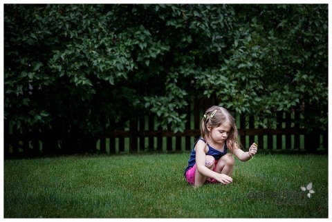 Color lifestyle photography shot of young child picking dandelions