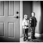 Dramatic black and white of young siblings posing by family door for in home portrait