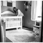 Mommy in little baby girl room smiling at baby in crib by Naperville and Chicago family photographer