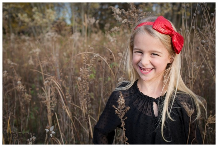 Beautiful girl with red bow in field session
